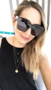 girl in black dress with black sunglasses and layered delicate necklaces
