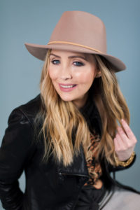 girl with a tan hat, long blonde hair and wearing a black faux leather jacket